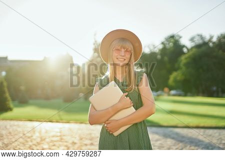 Adorable Young Blonde University Or College Student Girl With Laptop Wearing Green Dress And Hat In