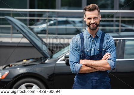 Positive Mechanic In Overalls Looking At Camera Near Blurred Car