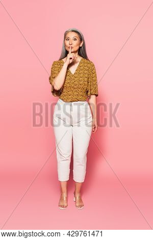Mature Woman In Trendy Clothes Looking At Camera And Showing Hush Sign On Pink