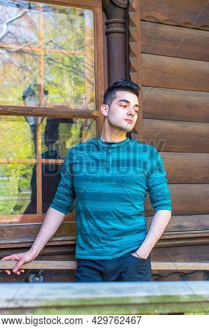 Dressing In A Green Striped Long Sleeves Henley Shirt, A Young Handsome Guy Is Standing By A Window