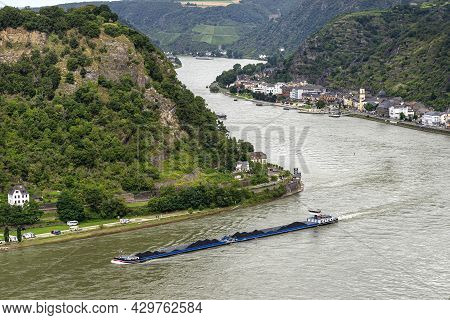 A Barge With Coal Sailing On The River Rhine In Western Germany, Visible Buildings On The River Bank