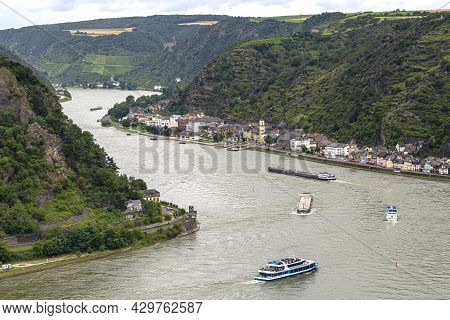 Tourist Ships And Barges Sailing On The River Rhine In Western Germany, Visible Buildings And Hills.