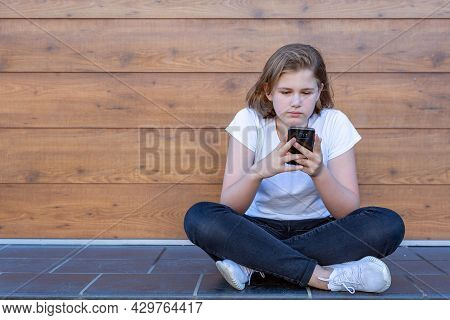 A Teenage Girl Focused On The Screen And Interacting With A Smartphone, Sitting Cross-legged On The