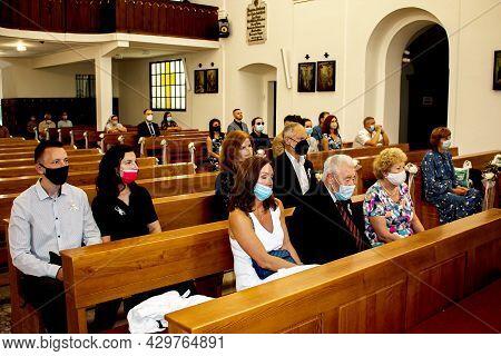 Nitra, Slovakia - 07.12.2021: People In Medical Masks At A Catholic Church. Coronavirus Pandemic.