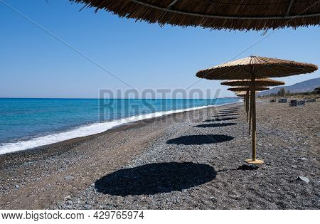 Tropical Beach Umbrellas Providing Sunshade For Swimmers At An Empty Beach. Summer Vacations. Paphos