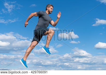 Energetic Man Athlete With Muscular Body Run In Sportswear Outdoor On Sky Background, Motivation.