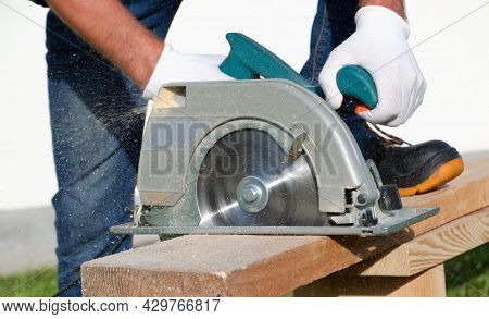 A Male Joiner Works With A Hand-held Circular Saw. A Builder Is Sawing A Board At The Construction S