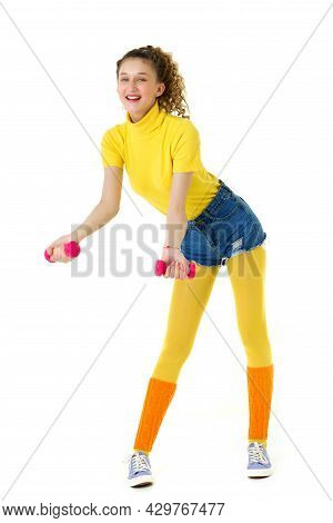 Happy Slim Girl Doing Aerobics With Red Dumbbells. Full Length Portrait Of Curly Girl Looking Stylis