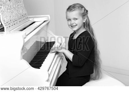 Beautiful Little Girl Playing On White Grand Piano. Black And White Shot Of Pretty Long Haired Girl