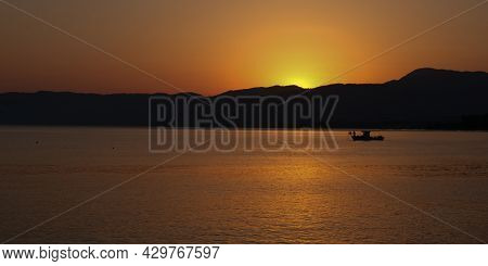 Fishing Boat Sailing In The Sea To Catch Fish At Sunrise. Latsi Paphos Cyprus