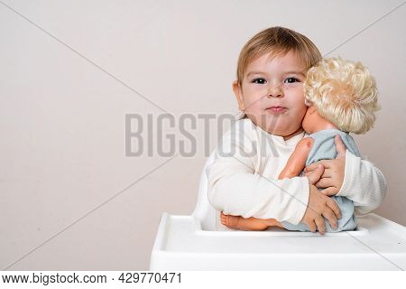 Baby Toddler Hugs With Old-fashioned Doll On A Studio Shot. Funny Serious Face. Best Friend Toy. Rol