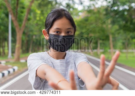 Portrait Asian Pretty Teen Girl In Casual Dress Wears Black Protective Mask Posing Gesturing With He