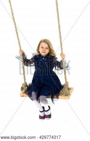 Lovely Blonde Little Girl Swinging On Rope Swing. Sweet Beautiful Girl Wearing Nice Blue Dress Sitti