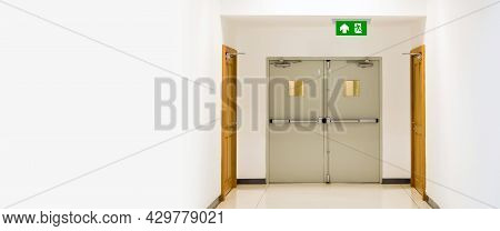 Green Emergency Fire Exit Sign Or Fire Escape With The Doorway Or Door Exit And Fire Hose Cabinet In