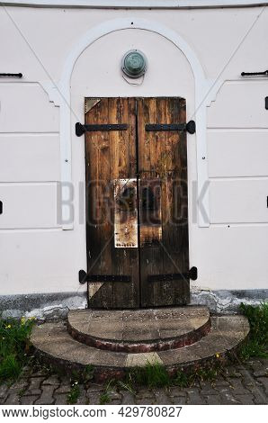 Old Wooden Door. Door With Forged Metal Hinges. Entrance To An Old Stone House With A Wooden Door.