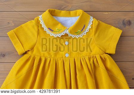 A Beautiful Children's Dress Made Of Natural Cotton With Embroidery Of Purple Flowers On The Collar.