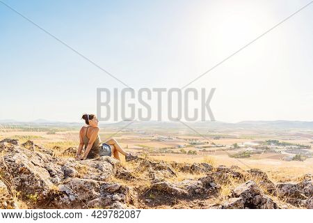 Woman Sitting On A Hill Overlooking The Landscape