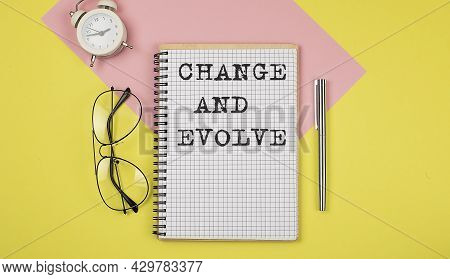 Change And Evolve On Notepad With Pen, Glasses And Alarm Clock