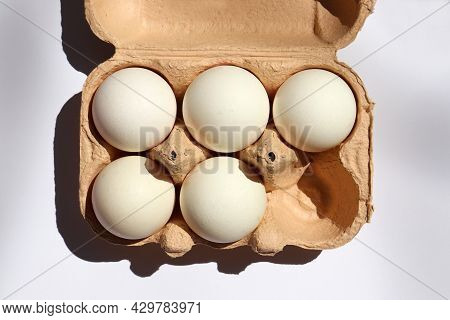White Eggs In A Carton Box On White Background. Hard Light, Shadows. Top View, Copy Space