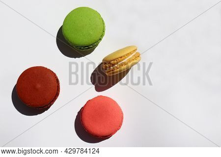 Colorful Macaroons On White Background. Hard Light, Shadow. Top View, Copy Space.