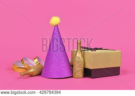 Purple Party Hat, Gift Box Small Golden Champagne Bottles And Party Streamers On Pink Background
