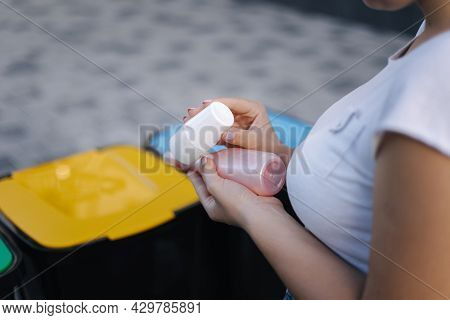 Woman Throwing Out In Recycling Bin Washed And Empty Shampoo And Deodorant Bottles. Female Looks At