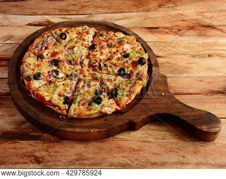 Veg Pizza On Wooden Pizza Board, Isolated Over A Rustic Wooden Background, Selective Focus