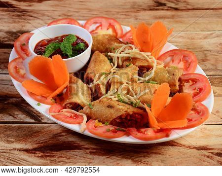 Veg Spring Rolls With Sweet Chili Sauce From A Asian Cuisine. Served Over A Rustic Wooden Table. Sel