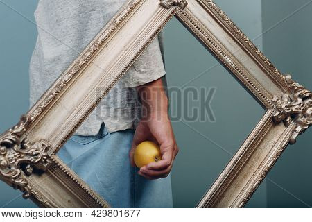 Millenial Young Man Holds Apple On Hand Palm In Gilded Picture Frame