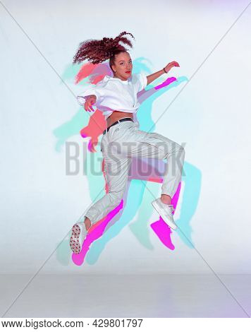Jumping Mixed Race Young Girl Dance In Colourful Light. Female Dancer Performer Jump Dancing Fiery H