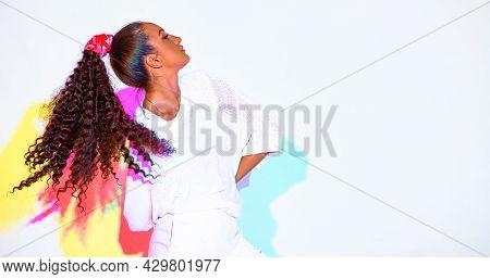 Beautiful Mixed Race Young Girl With Waving Afro Hairs In Colourful Rainbow Light On White Backgroun