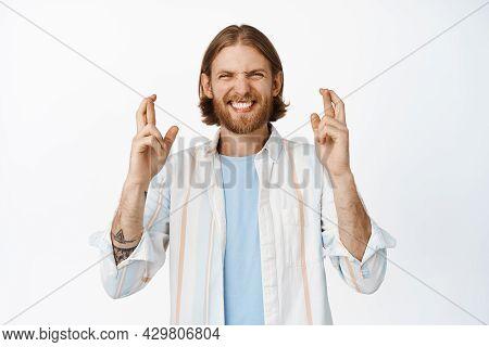 Hopeful Blond Man, Guy Having Faith, Making Wish, Cross Fingers Good Luck And Smiling Optimistic, St