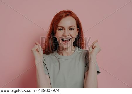 Young Overjoyed Redhead Woman Raising Hands Up With Clenched Fists, Doing Champion Gesture, Shouting