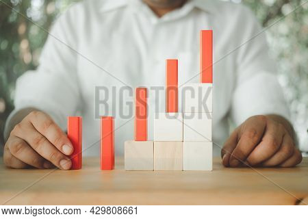Close-up View Of Man Putting Red Block On Staircase. A Metaphor To Management And Business Organizat