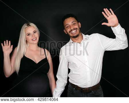 Portrait Of A Stylish, Proud And Happy Multi-ethnic Couple Expecting A Baby And Waiving Joyfuly