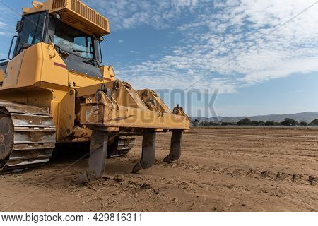 Heavy Grading Equipment Vehicles Resting Its Claws On The Hard Packed Dirt That Has Been Graded Down