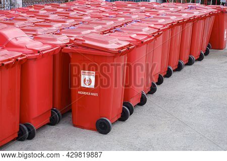 Rows Of Red Hazardous Waste Bins Are Neatly Packed With Rubbish From Covid-19 Patients Behind The Fi