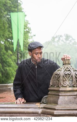 In The Raining, A Young Handsome Black Guy Is Standing Outside And Into Deeply Thinking