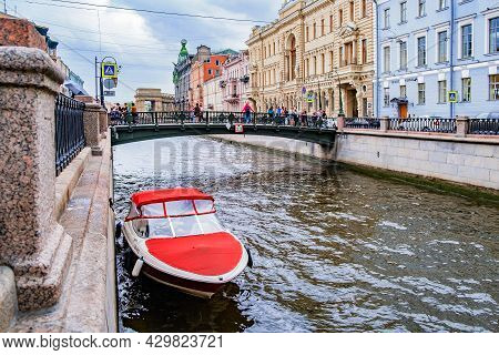 Canal In St. Petersburg, Russiarivers And Canals Of St. Petersburg. A Pleasure Boat With A Red Awnin