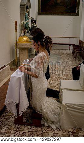 Nitra, Slovakia - 07.12.2021: Catholic Wedding Amid The Coronavirus Pandemic. The Bride And Groom Kn