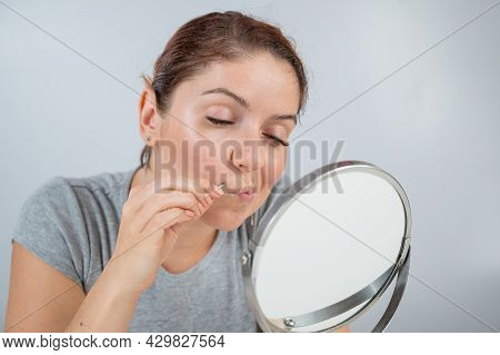 Caucasian Woman Looks In The Mirror And Removes The Mustache Herself With The Help Of Tweezers. Hirs