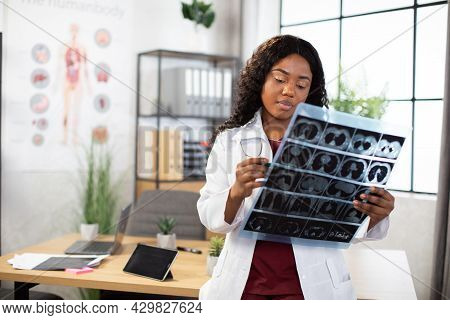 Young Attractive African American Female Doctor Radiologist Looking At X-ray Image, While Standing I