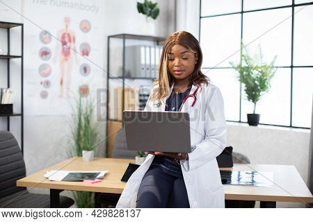Female African American Doctor Working With Patients Charts And Records On Laptop Computer Alone In
