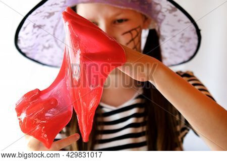 Cute Girl Playing With A Red Bloody Glitter Slime. She Is Having Fun And Making Faces. Adorable Girl