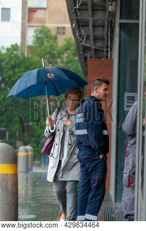 Timisoara, Romania - May 25, 2016: Woman With An Umbralla Walking In The Rain. Real People.