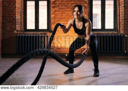 Fitness Young Athletic Woman With Strong Beautiful Body In Black Sportswear Exercising With Battle R