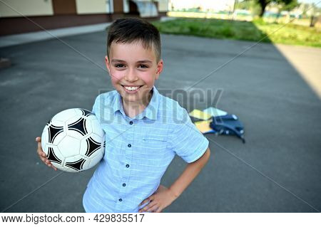 Handsome Cheerful Schoolboy With Soccer Ball In Hands Smiling With Toothy Smile On The Background Of