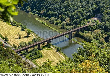 The Steel Truss Structure Of The Railway Bridge Seen From Above, In The Background There Are Hills O