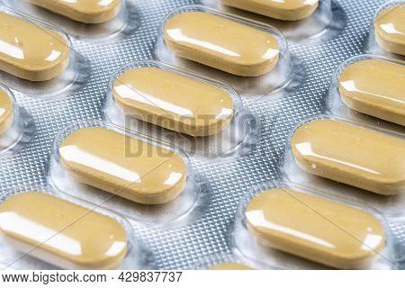 Macro Shot Pile Of Yellow Tablets Pill In Blister Packaging Background. Aluminium Foil Blister Pack.