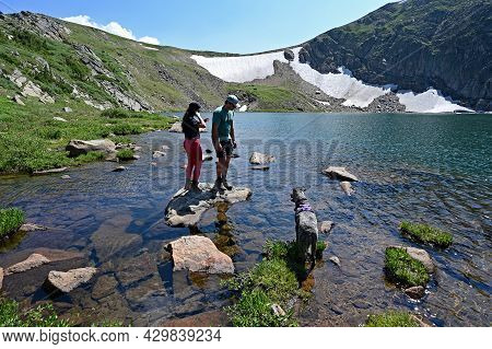 Young Couple And Dog On Shore Of King Lake In Indian Peaks Wilderness In Arapaho National Forest, Co